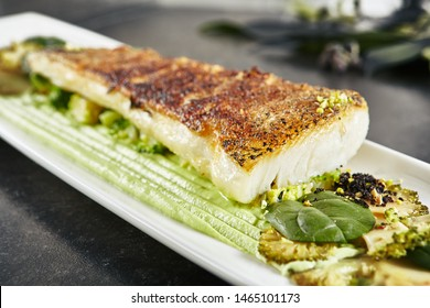 Beautiful Restaurant Plate of Baked Halibut Fillet and Broccoli in Different Textures  Close Up. Exquisite Italian Dish of Grilled Flatfish or Sole Fish on Natural Black Stone, Leaves Background