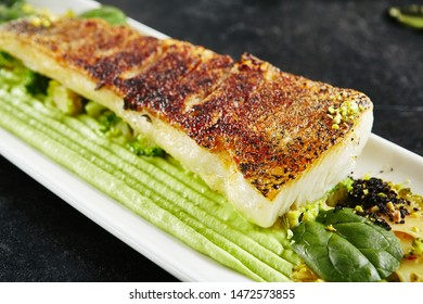Beautiful Restaurant Plate of Baked Halibut Fillet and Broccoli in Different Textures Closeup. Exquisite Italian Dish of Grilled Flatfish or Sole Fish on Natural Black Stone, Leaves Background
