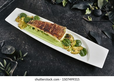 Beautiful Restaurant Plate of Baked Halibut Fillet and Broccoli in Different Textures. Exquisite Italian Dish of Grilled Flatfish or Sole Fish on Natural Black Stone, Leaves Background