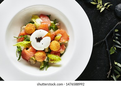 Beautiful Restaurant Plate of Trout Fillet 48 Degrees and Egg Poached with Warm Potatoes Top View. Exquisite Italian Arancino and Smoked Salmon or Sliced Red Fish on Natural Black Marble Background