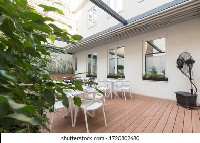 Hermoso restaurante terraza interior de verano con techo móvil