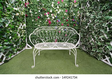 Beautiful retro bench near to green hedge with small flowers.