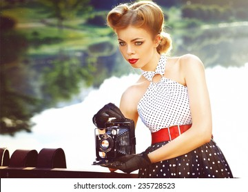 beautiful retro girl in vintage clothing with vintage camera in hand near the lake