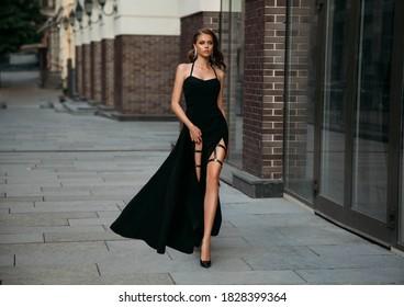 beautiful retro sexy fashion model. lady walks down old city street. young woman in classic evening black luxury dress. glamour stylish girl, long bare leg. Elegant makeup, long wavy hair pretty face