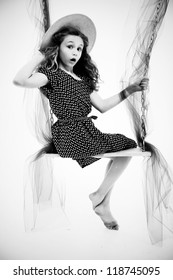 Beautiful retro style portait of nine year old girl in dress and summer hat on swing over white.