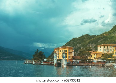Beautiful retro toned cityscape of coastline of Italian city with Como lake, building, big trees, green mountain and dramatic sky before the rain