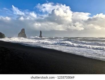 Beautiful Reynisfjara Black Sand Beach in a cloudy day: Vik Village, Iceland.