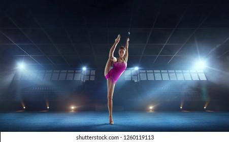 Beautiful rhythmic gymnast in professional arena.