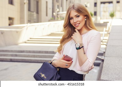 3239fb6f98 Beautiful rich casual blonde stylish fashion business woman with a phone in  her hand working in