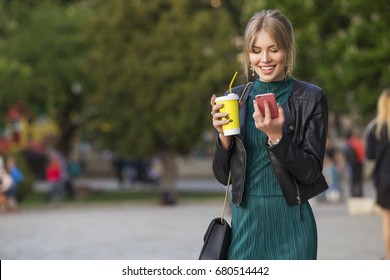 Beautiful rich luxury looking blonde caucasian business woman in casual green outfit standing on a european streets, holding coffee and talking on a phone. Daylight, outdoors.