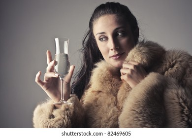 Beautiful rich woman holding a glass of champagne