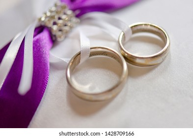 Beautiful Ring Pillow With Two Golden Wedding Rings And Violet Decoration