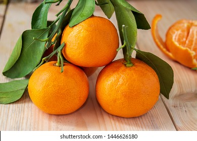 beautiful ripe tangerines with green leaves on wooden background