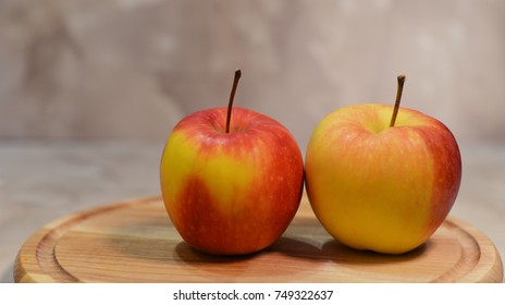 Beautiful ripe yellow and red apples on a wooden board
