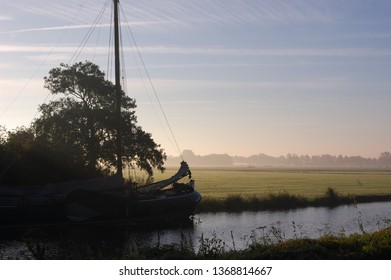 beautiful river with cloured sky and sun in the background, silhouette from a stunning dutch barge