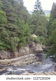 Beautiful river flowing along rocks in a treed ravine in Scotland.