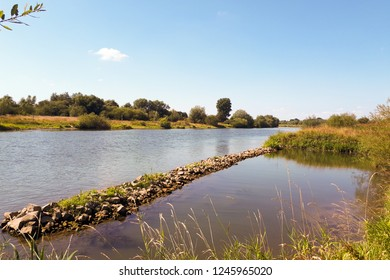 A beautiful river landscape. Flowing river that reflects the sky and plants on the shore. The shore is lined with stone