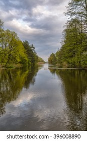 beautiful river landscape with trees and clouds reflections