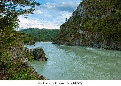 Beautiful river landscape. Turquoise Katun river flowing in the valley between the rocks. On the banks of the lush greenery of trees, shrubs. On the background of mountains. Mountain Altai, Russia