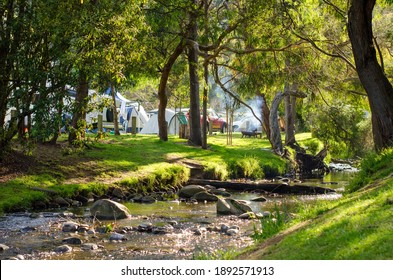 The beautiful riverbank of a small flowing river with some camping tents and fire pits in the background. Concept of outdoor adventure, family holiday and summer holiday fun. Wye River, VIC Australia