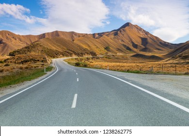 Beautiful road acroos the golden grass hill of Lidis Pass of south island, New Zealand