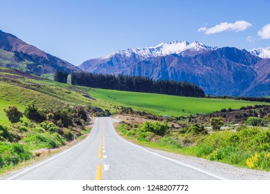 Beautiful road on the grass hill with snow capped moutain as a background in New Zealand