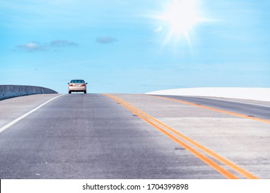 Beautiful road towards the sky with one car along the lane.