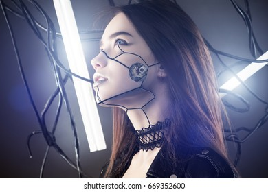 beautiful robot girl in cyberpunk style looking up on background of wires and glowing lamps