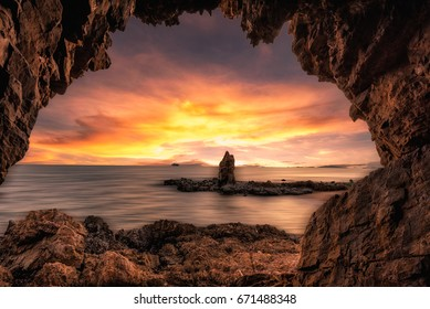The beautiful rock cave at the sea with sunrise sunset