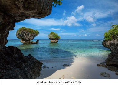 Beautiful rock formations along the sandy beach of Tanguisson Beach on the tropical island of Guam during the morning calm of the ocean on a clear, sunny day