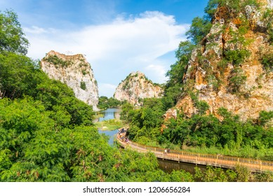 Beautiful rock mountain or hill landscape with clear lake and long walkway in sunny day blue sky. Asia travel destination concept, Ratchaburi Thailand. Traveling on holiday vacation summer season.