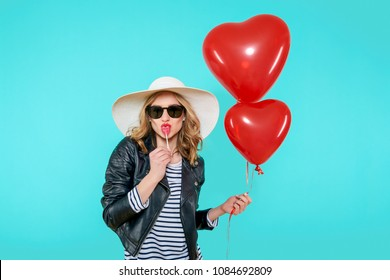 Beautiful rocker girl in leather jacket and summer hat kissing heart shaped lolipop and holding heart shaped balloons. Attractive cool young woman fashion portrait over pastel blue background.