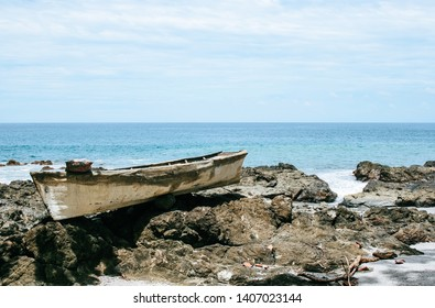Beautiful rocky beach with a deserted, old boat in Montezuma, Costa Rica