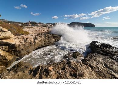 Beautiful rocky coastline with waves breaking  in Moraira, Costa Blanca, Spain
