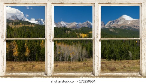 A beautiful Rocky Mountain Continental Divide rustic picture window frame panorama view with clouds hanging on the mountains, a light dusting of snow and fall colors in the air.