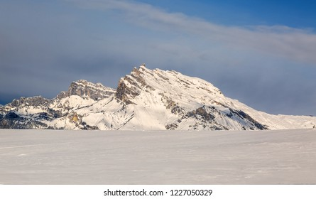 Beautiful rocky mountain peak covered by snow over a ski slope in the Alps in Mont Blanc Massif.