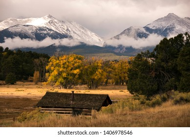 Beautiful Rocky Mountains of Colorado on a fall day with golden leaves of autumn colors with snowcapped peaks of the rugged mountain range behind on a ranch farm homestead near Salida / Buena Vista