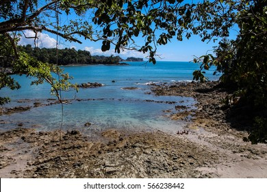Beautiful rocky tropical beach landscape framed by foliage