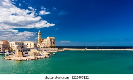 The beautiful Romanesque Cathedral Basilica of San Nicola Pellegrino, in Trani. Construction in limestone tuff stone, pink and white. A pointed arch under the bell tower. Italy, Puglia, Bari, Barletta