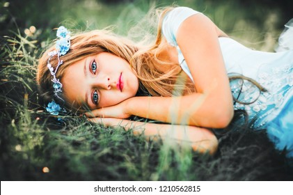 Beautiful romantic blonde girl with blue  eyes posing in forest. Dreaming princess in fairy blue dress and hair accessories enjoying nature. Fairytale and fantasy work.