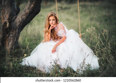 Beautiful romantic blonde girl with blue  eyes posing in forest. Dreaming princess in fairy white dress enjoying nature on a swing. Fairytale and fantasy work.