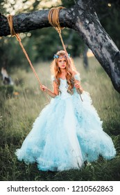 Beautiful romantic blonde girl with blue  eyes posing in forest. Dreaming princess in fairy blue dress and hair accessories enjoying nature on swing. Fairytale and fantasy work.
