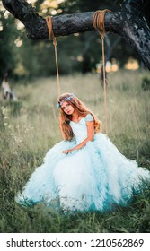 Beautiful romantic blonde girl with blue  eyes posing in forest. Dreaming princess in fairy blue dress and hair accessories enjoying nature with swing. Fairytale and fantasy work.