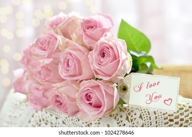 beautiful romantic bouquet of pink roses lying on shabby chic style chair