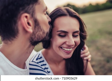 Beautiful romantic couple enjoying the company of each other outdoors. Handsome man kisses tenderly his beautiful young woman in cheek.