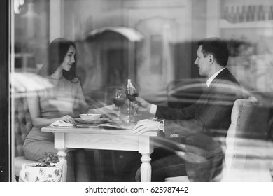 Beautiful romantic couple having dinner with wine in bright luxury restaurant. View through window from outside