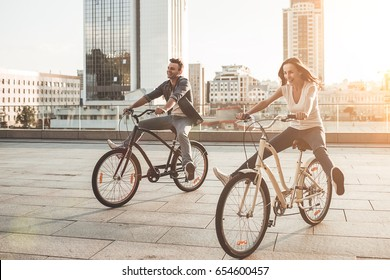 Beautiful romantic couple is having fun in the city with bicycles on the sunset. Enjoying the company of each other.