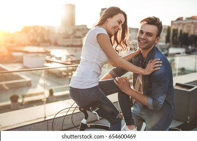 Beautiful romantic couple is having rest in the city with bicycles. Enjoying the company of each other.