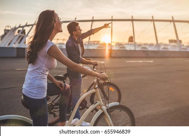 Beautiful romantic couple is having rest in the city with bicycles on the sunset. Enjoying the company of each other.