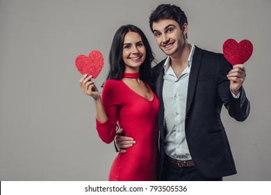 Beautiful romantic couple isolated on grey background. Attractive young woman in red dress and handsome man in suit are hugging with red hearts in hands. Happy Saint Valentine's Day!
